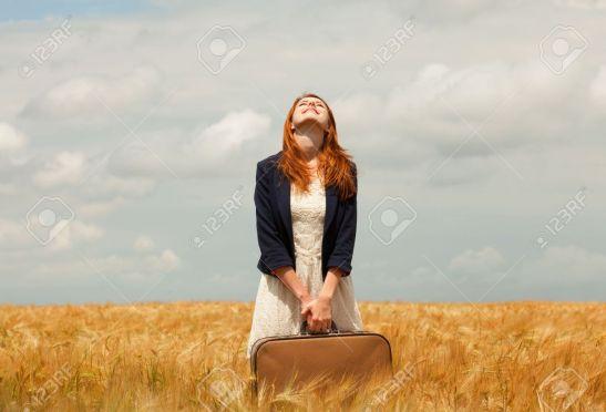 chica-pelirroja-con-maleta-en-campo-de-trigo-de-primavera